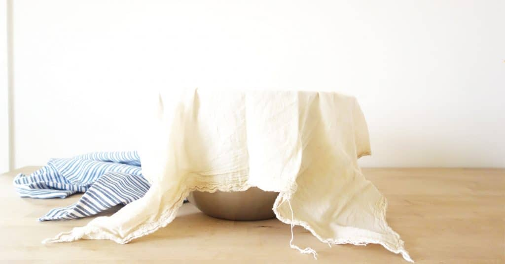 Yogurt in a cheesecloth draped over a bowl on a counter