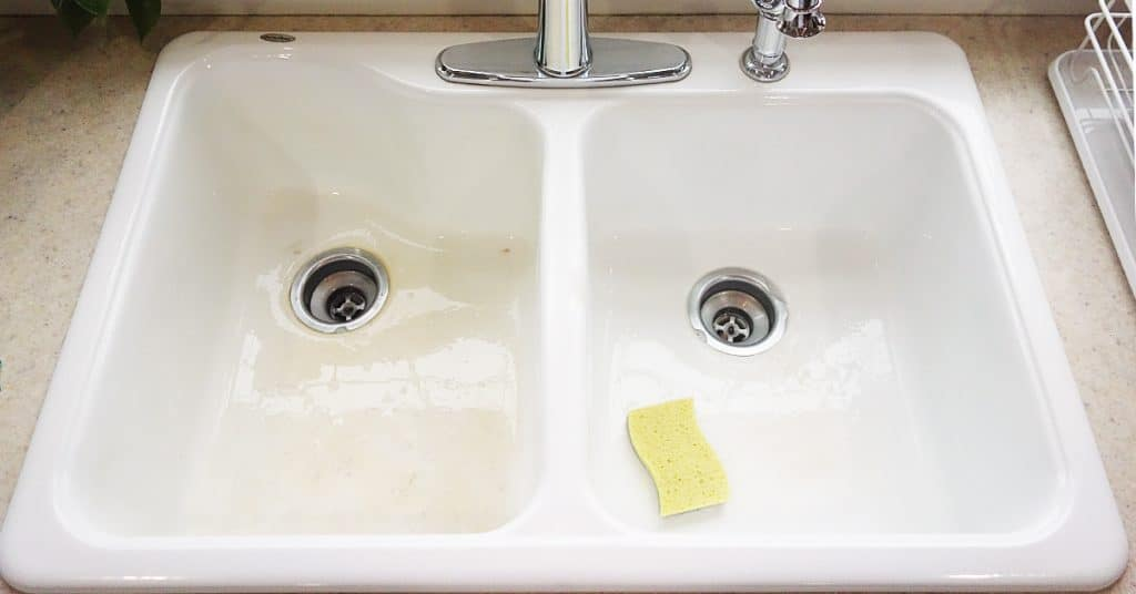 A white kitchen sink with a yellow scrubby in it