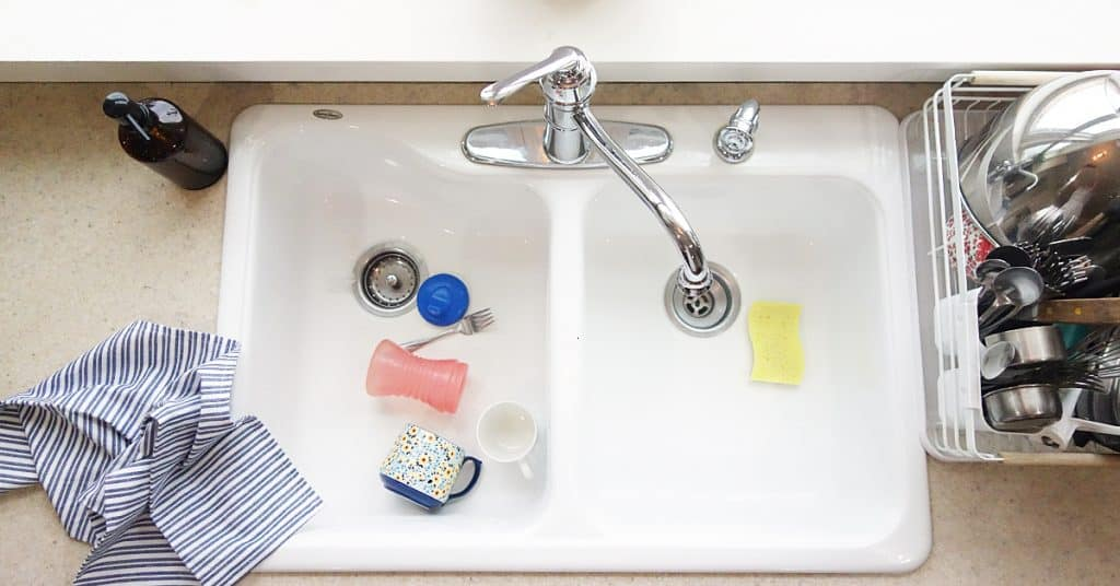 a white kitchen sink full of dirty dishes
