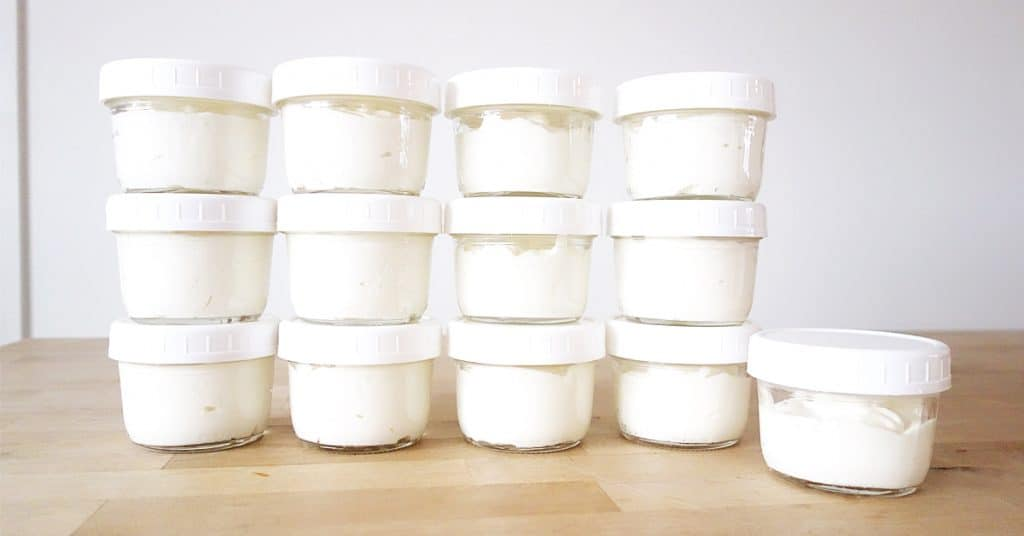 mason jars with lids of homemade honey yogurt lined up and stacked on a counter