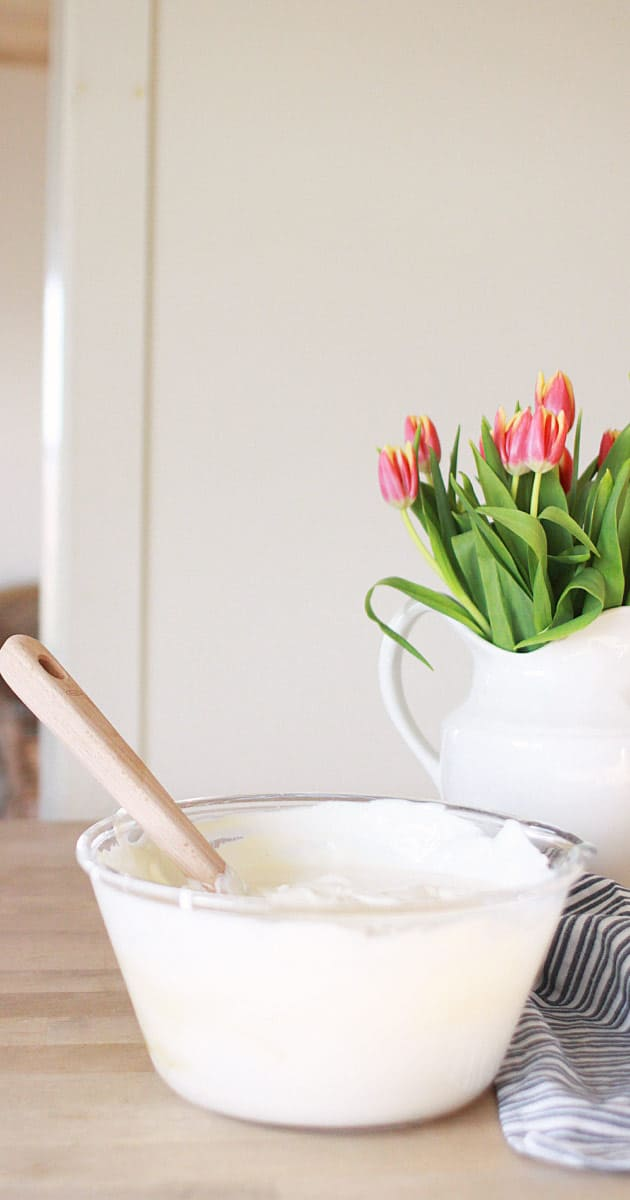 a bowl of homemade greek yogurt with a wooden spoon, striped dishtowel and a vase of tulips