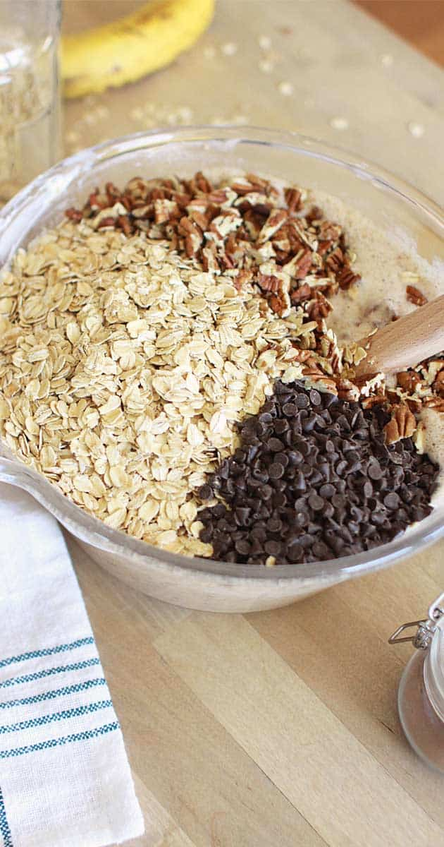oats, chocolate chips and pecans in a mixing bowl with a wooden spoon