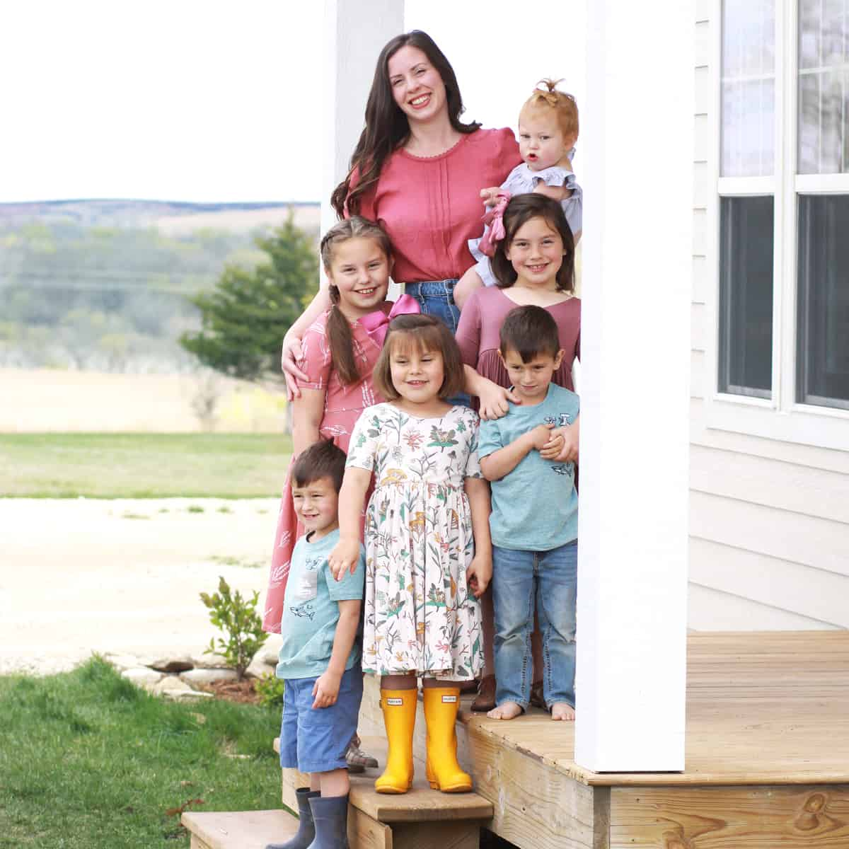 a large family with 6 kids on a front porch posed for a family photo