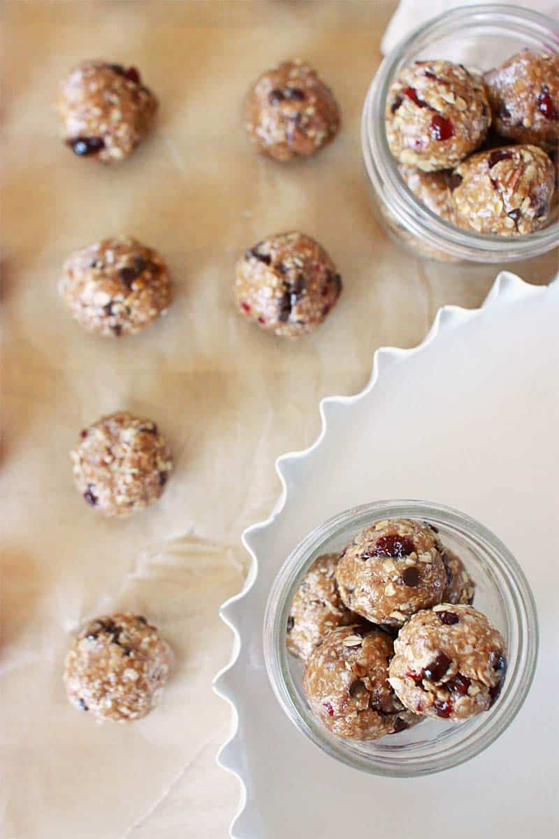 brown parchment paper with rows of granola balls with chocolate chips and craisins and some in mason jars