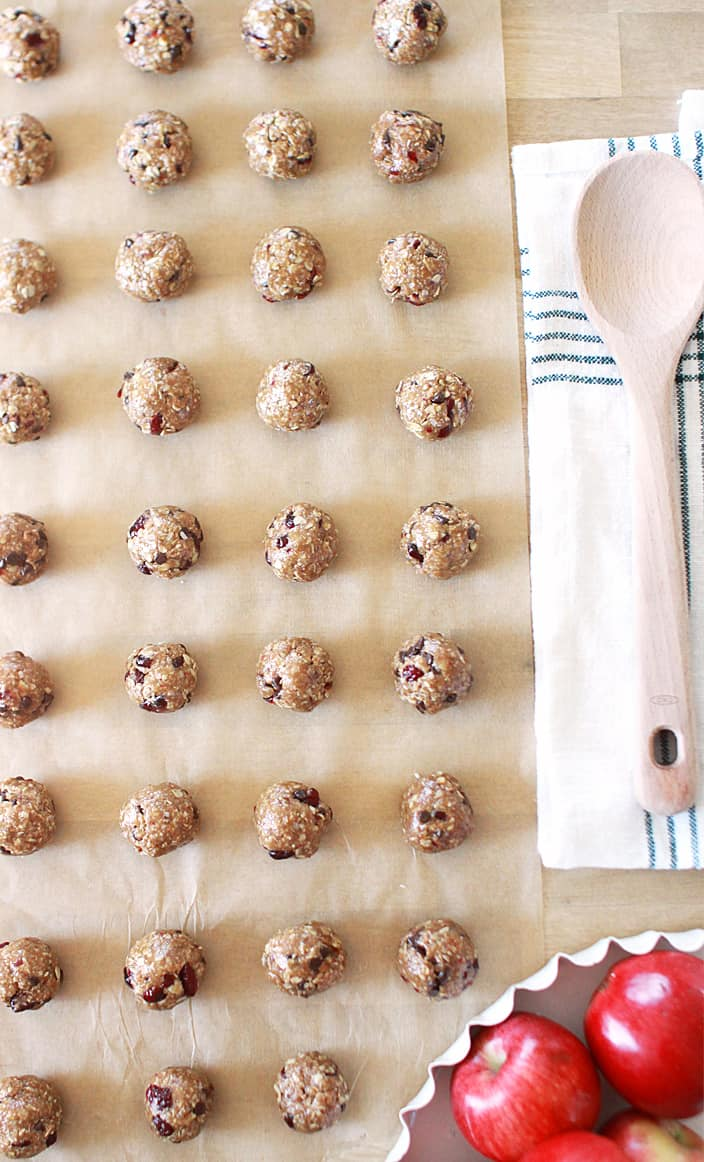 brown parchment paper with rows of granola balls with chocolate chips and craisins