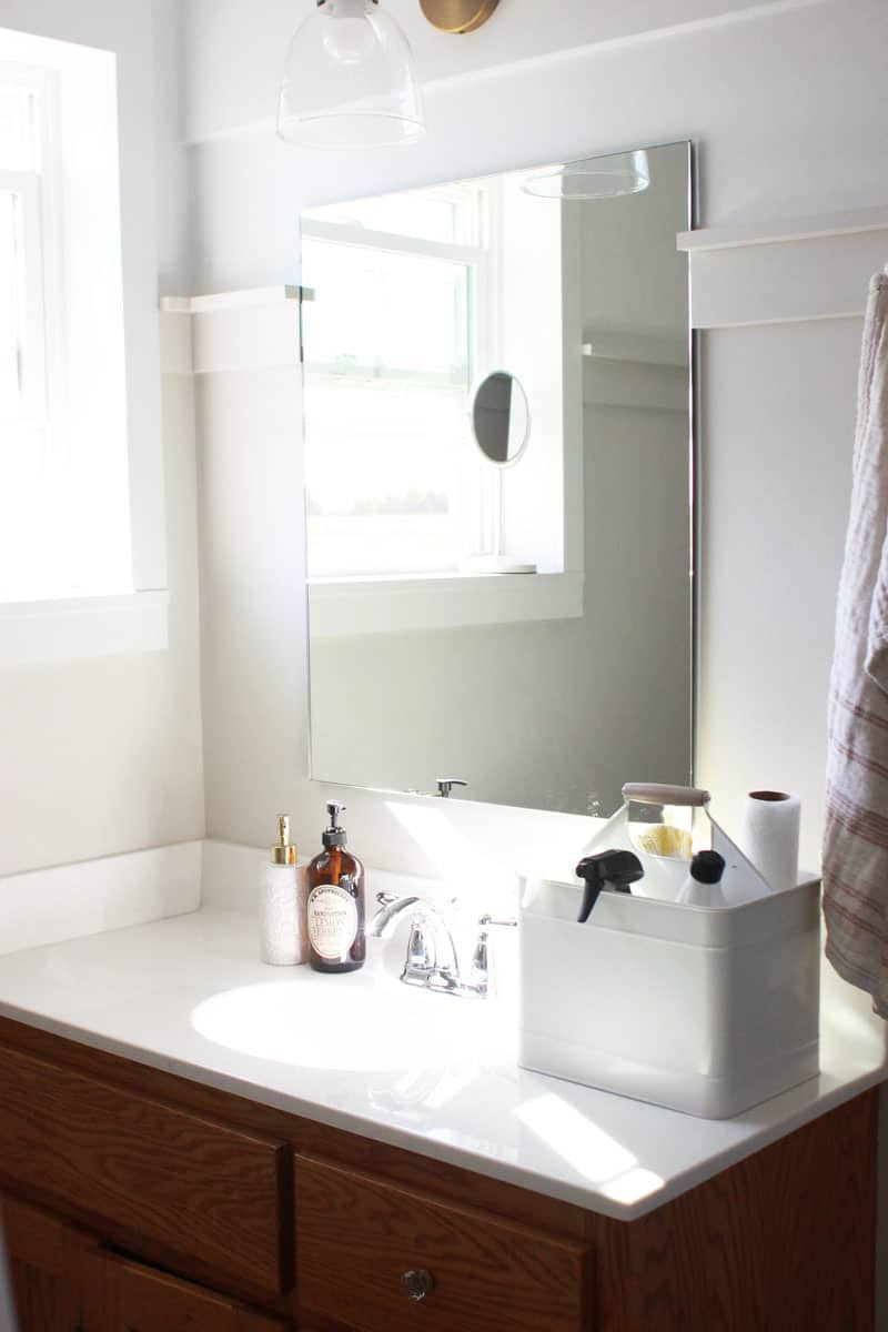 a white and cream minimalist bathroom with a cleaning caddy full of leaning supplies on the counter