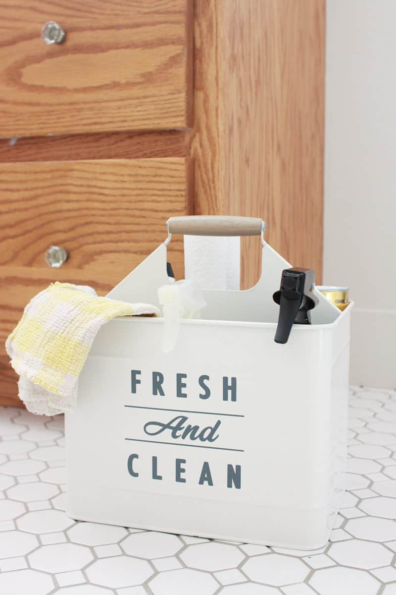a cleaning caddy full of cleaning supplies sitting on a bathroom floor
