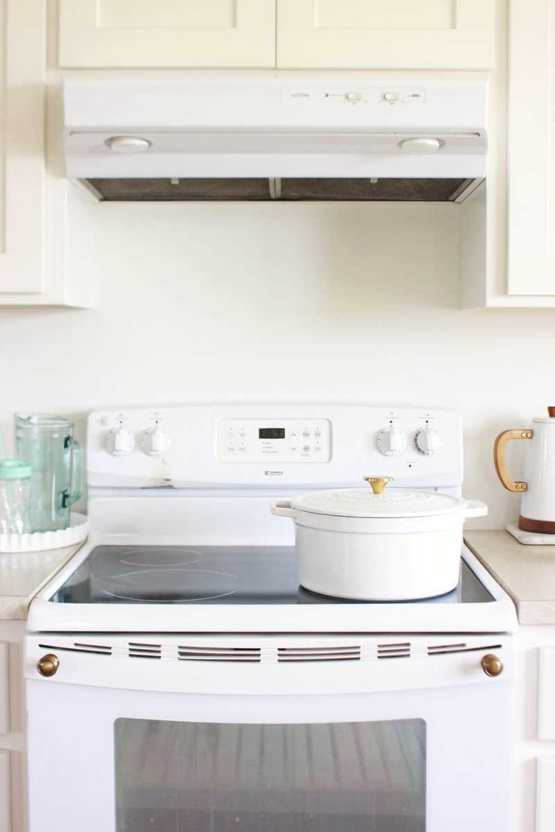 a clean shining black glass stovetop with a white Dutch oven on top and white kitchen cabinets