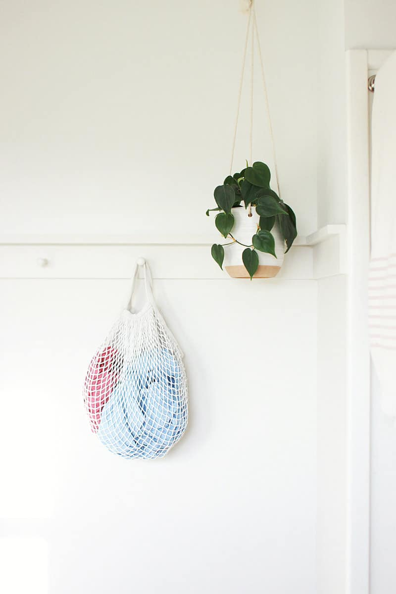 a bag of laundry hanging from a peg coat rack in a bathroom. a plant is hanging from the ceiling