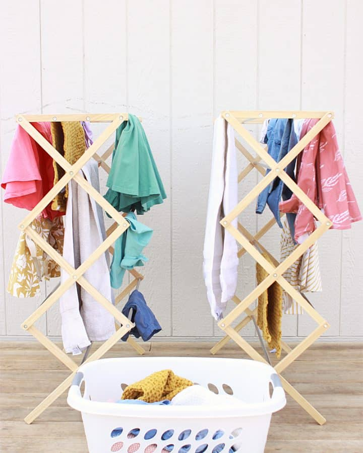 bamboo drying racks with clean clothes hanging from them on a deck