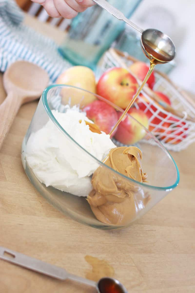 a bowl has a dollop of peanut butter and Greek yogurt. a hand is pouring in a Tablespoon of syrup. in the background is a basket of apples and a striped dish towel