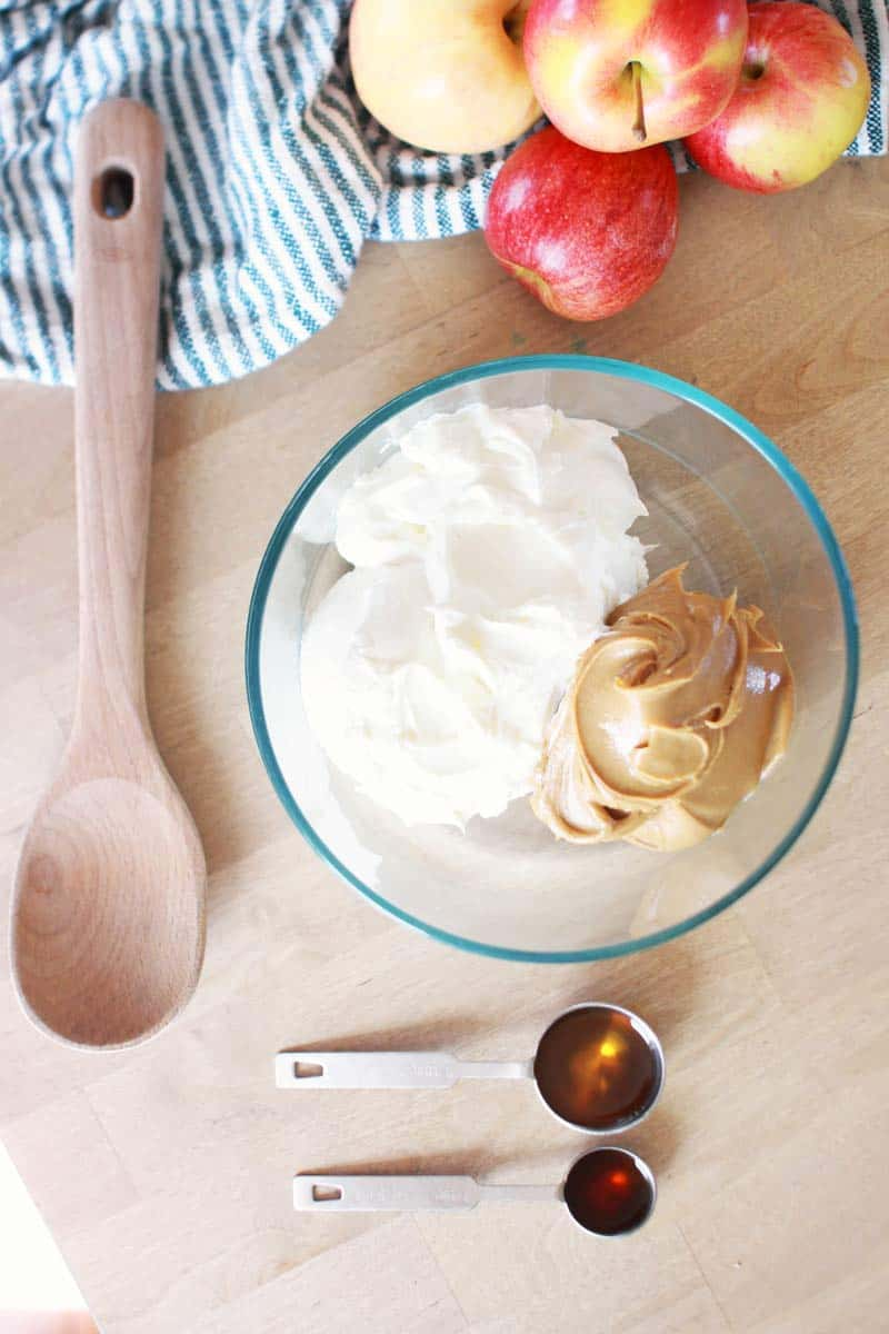 a bowl has a dollop of greek yogurt and peanut butter. a tablespoon of syrup and a teaspoon of vanilla extract