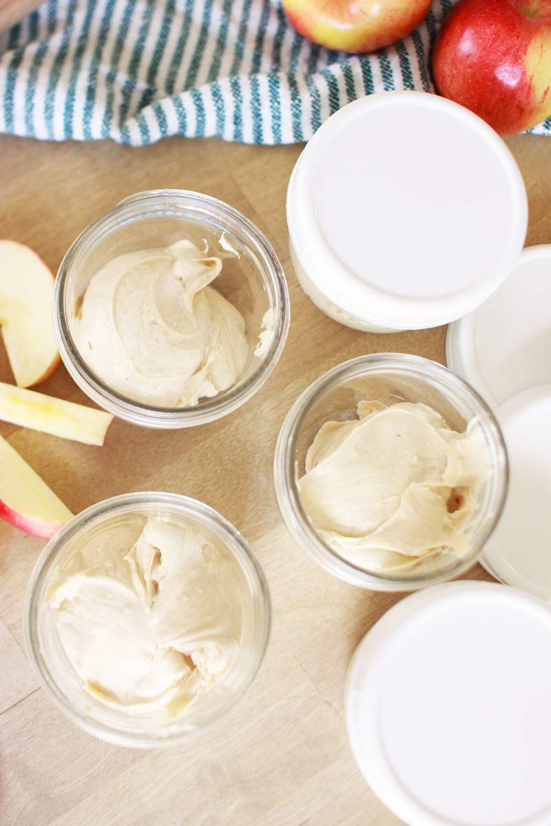individual mason jars of peanut butter yogurt dip. there are lids next to them and slices of apples