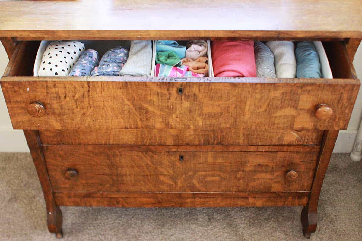 a dresser drawer filled with neatly folded girls' clothing in drawer dividers