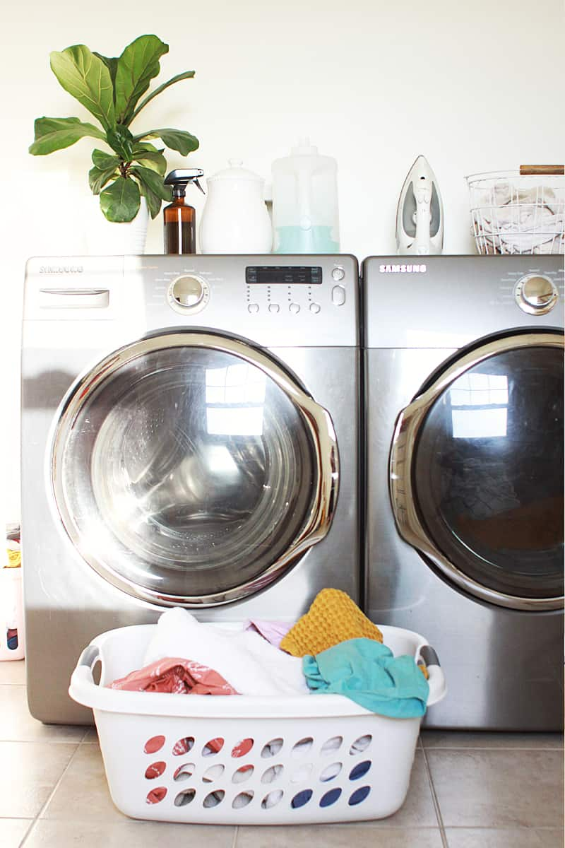 a washing machine and dryer with a laundry basket full of clean laundry