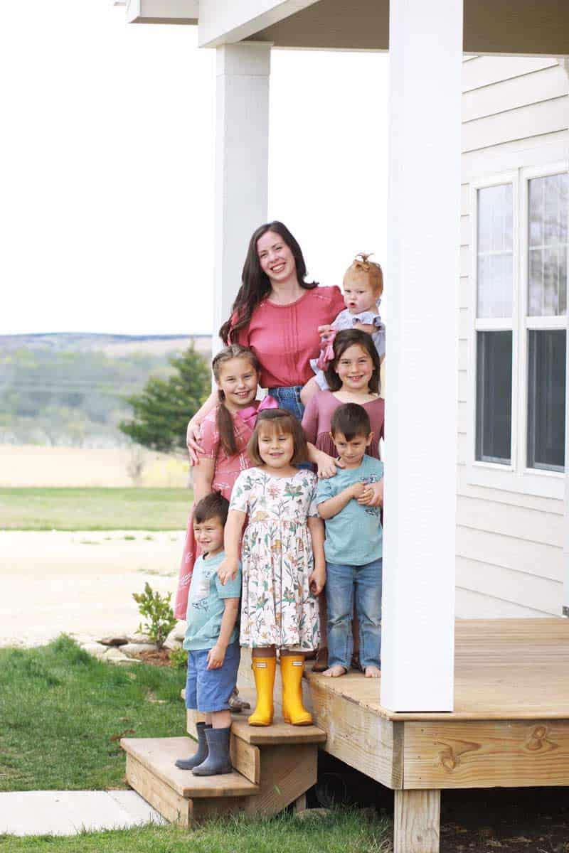 a large family with 6 kids posed on a front porch for a family photo