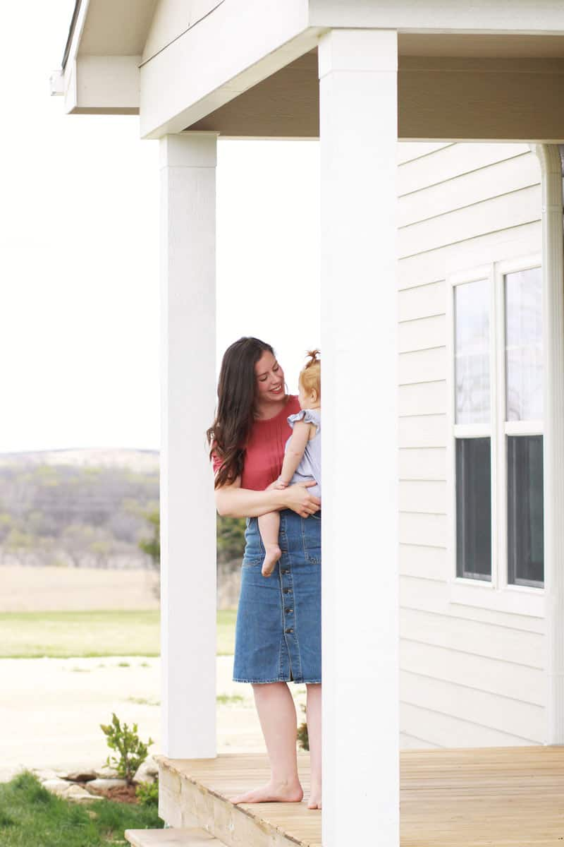 a mom looking at her baby on a front porch inn the country