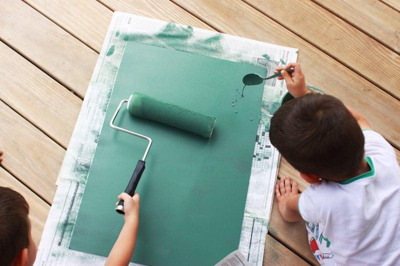 twin boys rolling green paint onto a board