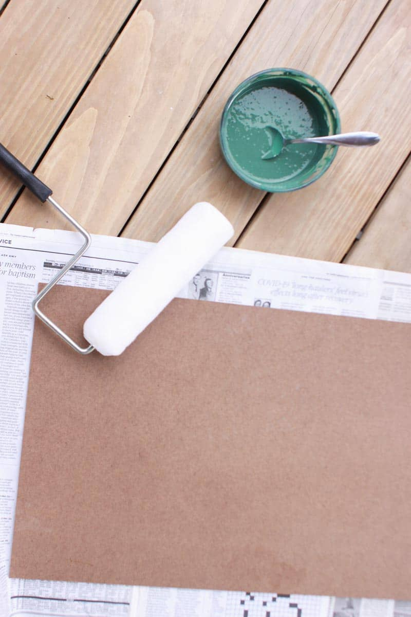 a clean paint roller, a board with newspaper underneath and a bowl of green paint