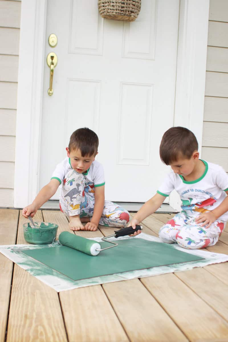 twin boys rolling green paint onto a DIY chalkboard