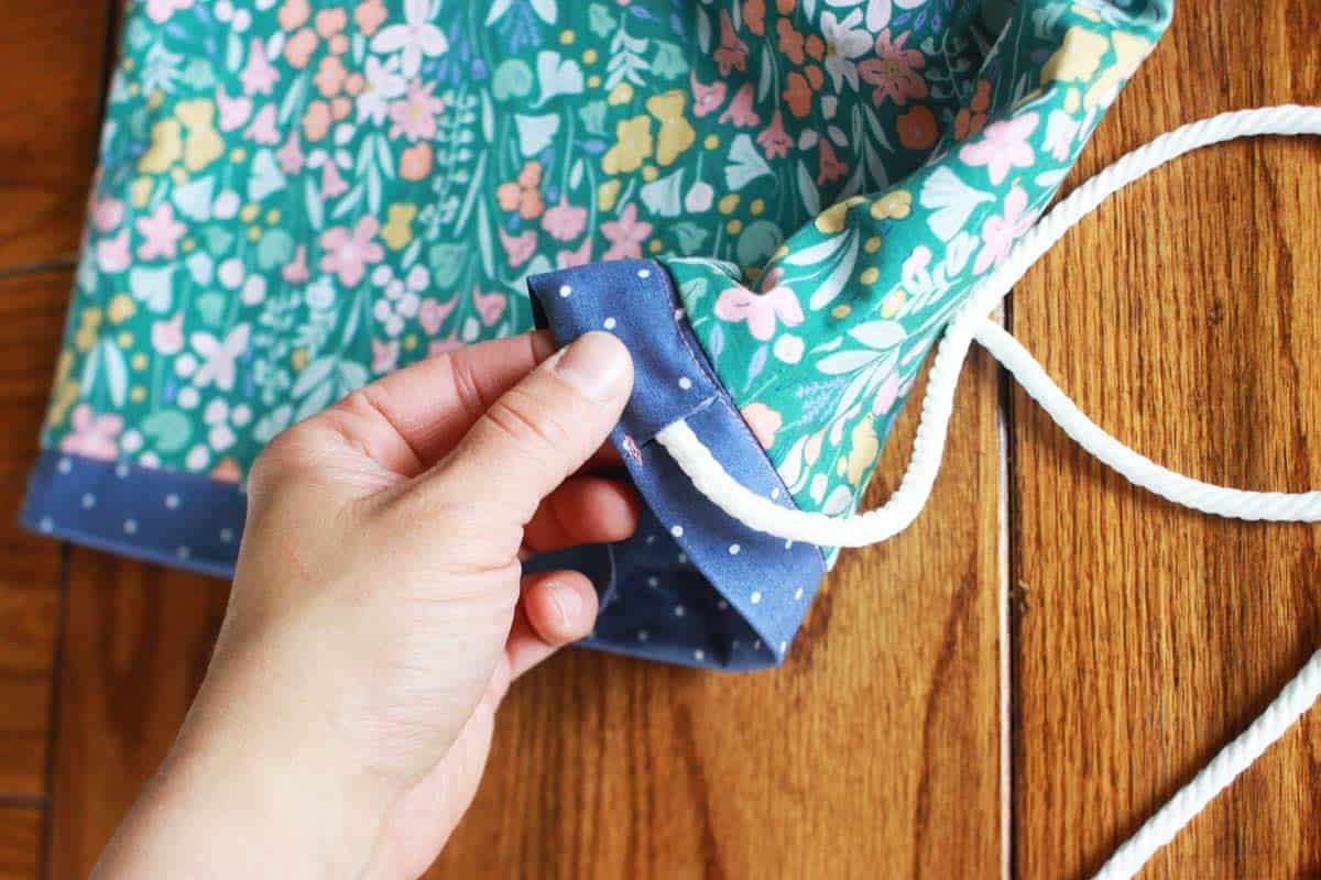 a photo showing straps being added to a drawstring backpack