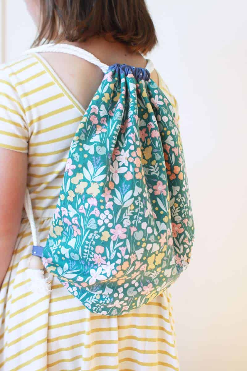 a girl wearing a lined drawstring backpack that is blue and green