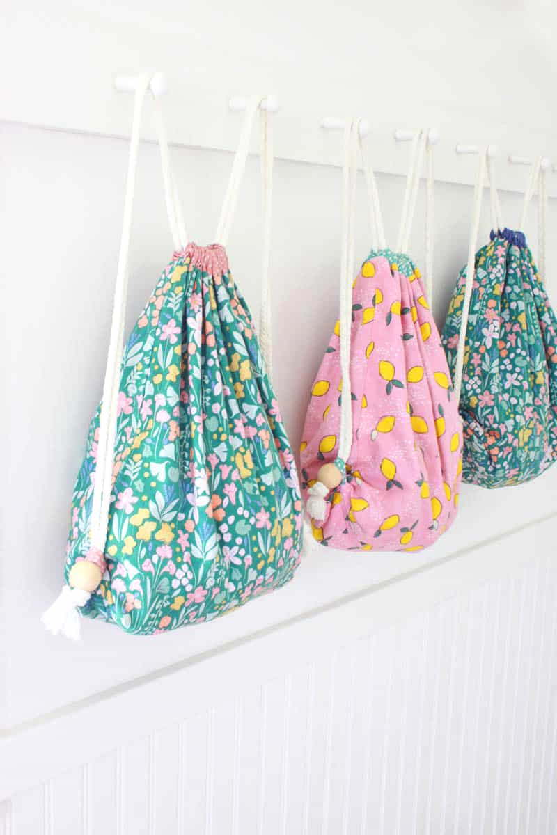 3 colorful lined drawstring backpacks lined up on a coat rack