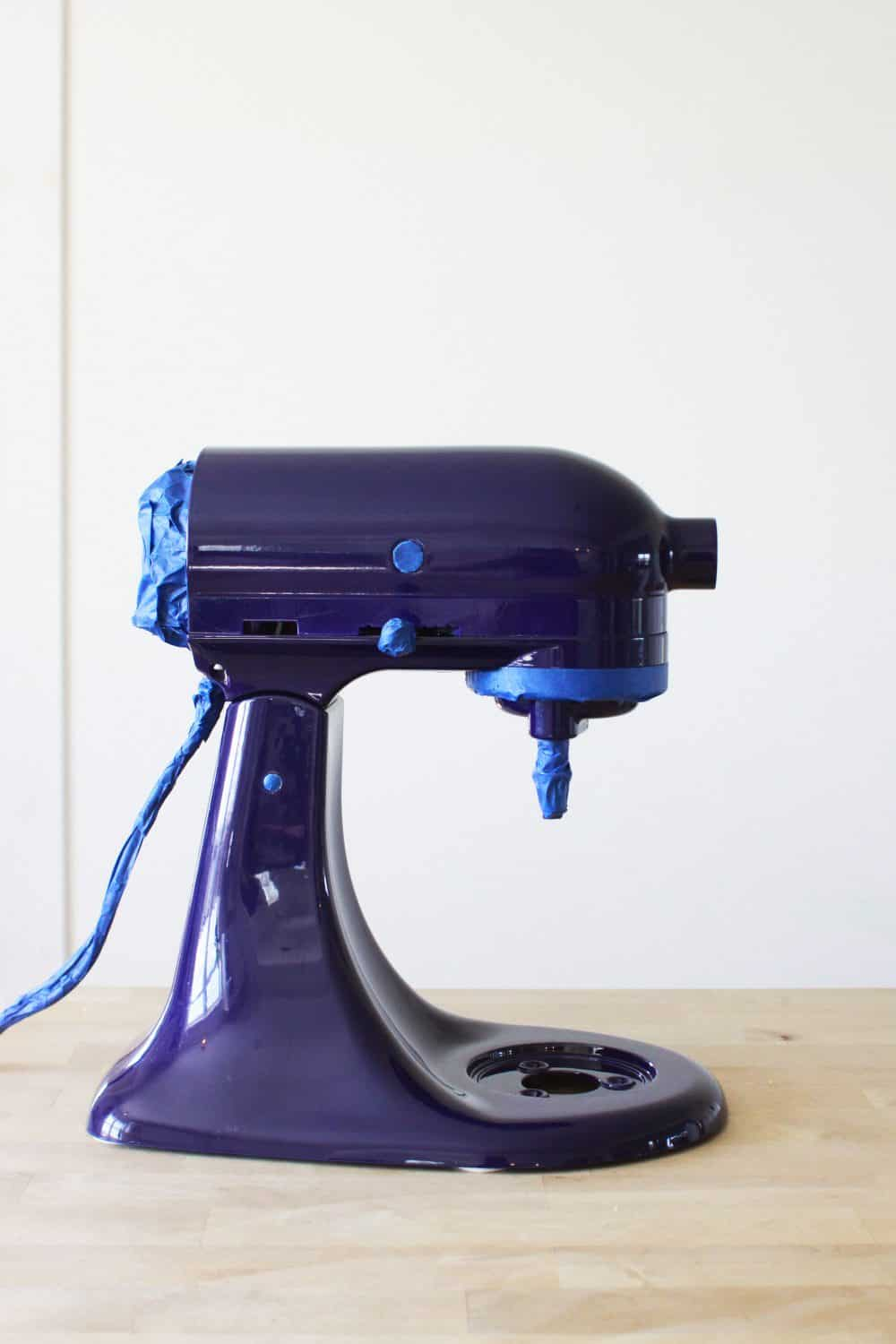 a royal blue KitchenAid mixer with parts taped off with blue painter's tape