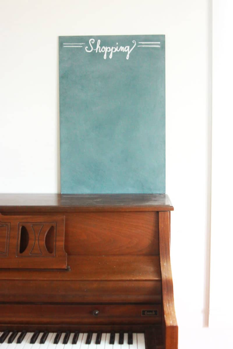 homemade chalkboard has shopping written in chalk across the top, is set on a piano