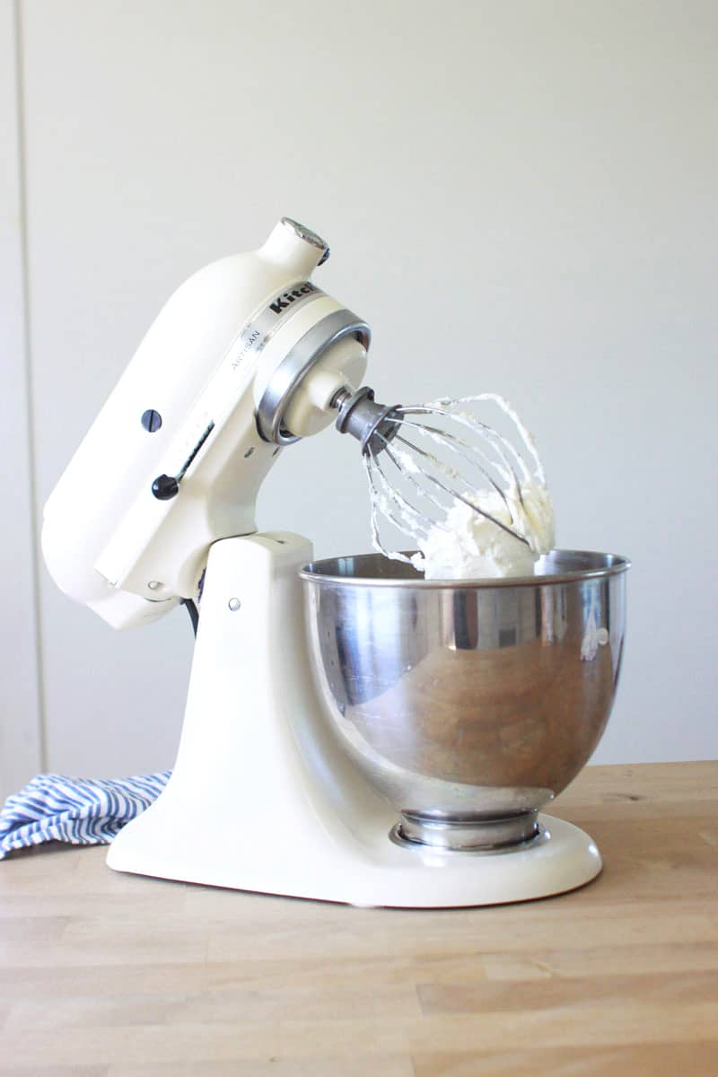 a white painted kitchenaid mixer on a butcher block countertop