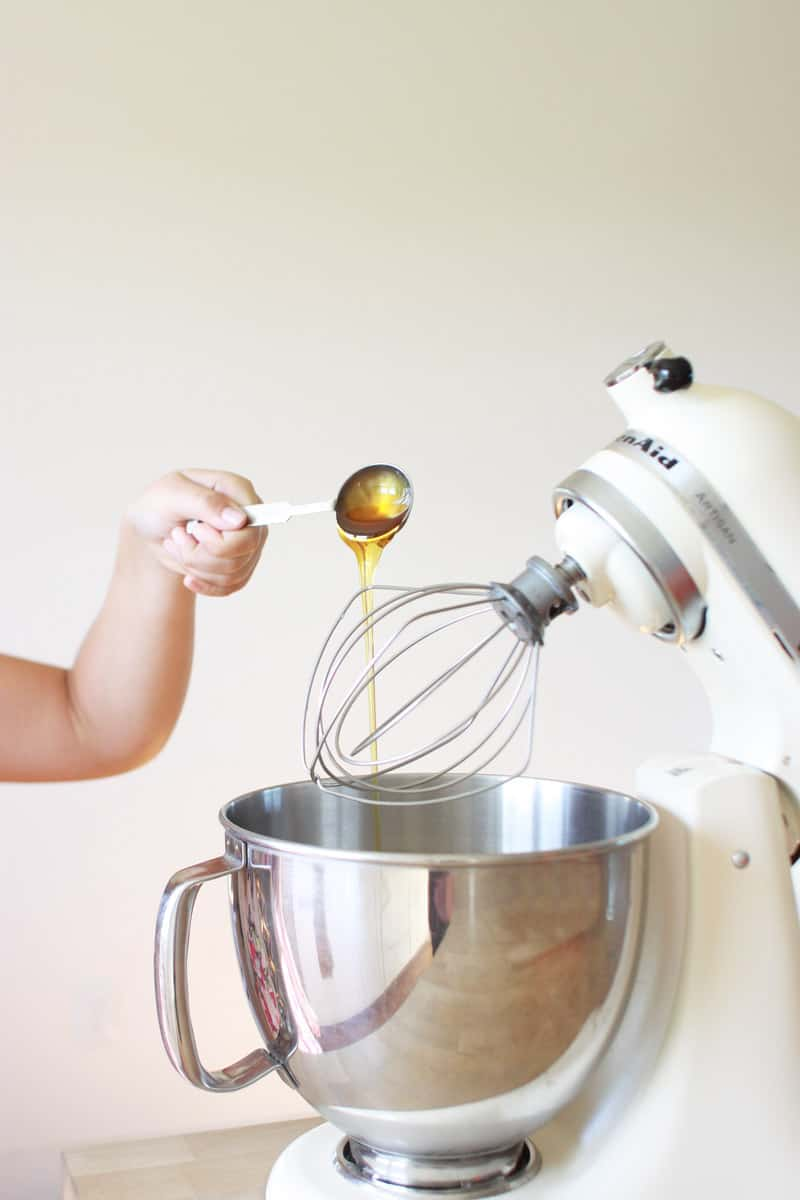 a cream colored kitchen aid mixer with the whisk attachment. a hand is pouring a spoonful of honey into the bowl