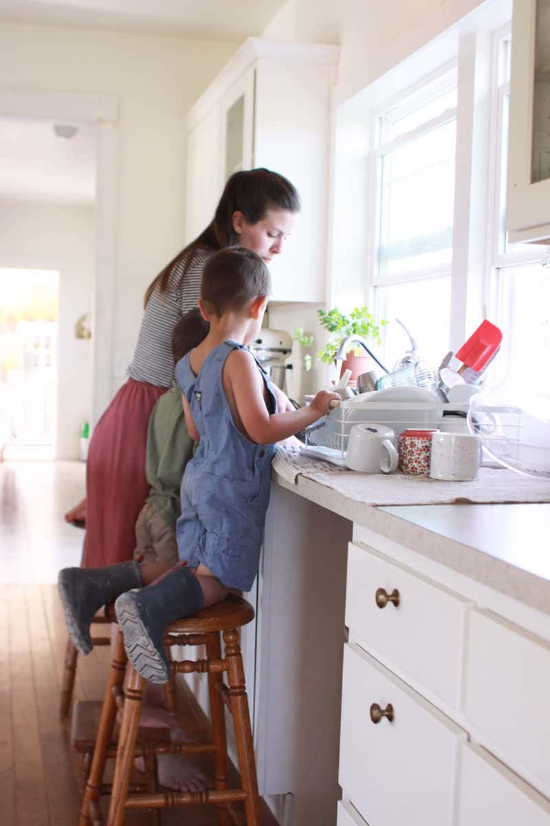 a mom washing dishes with her kids