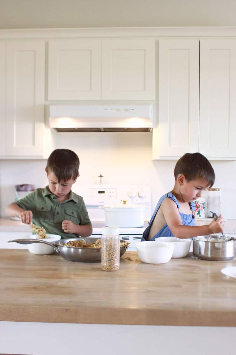 twin toddler boys making dinner at a kitchen island