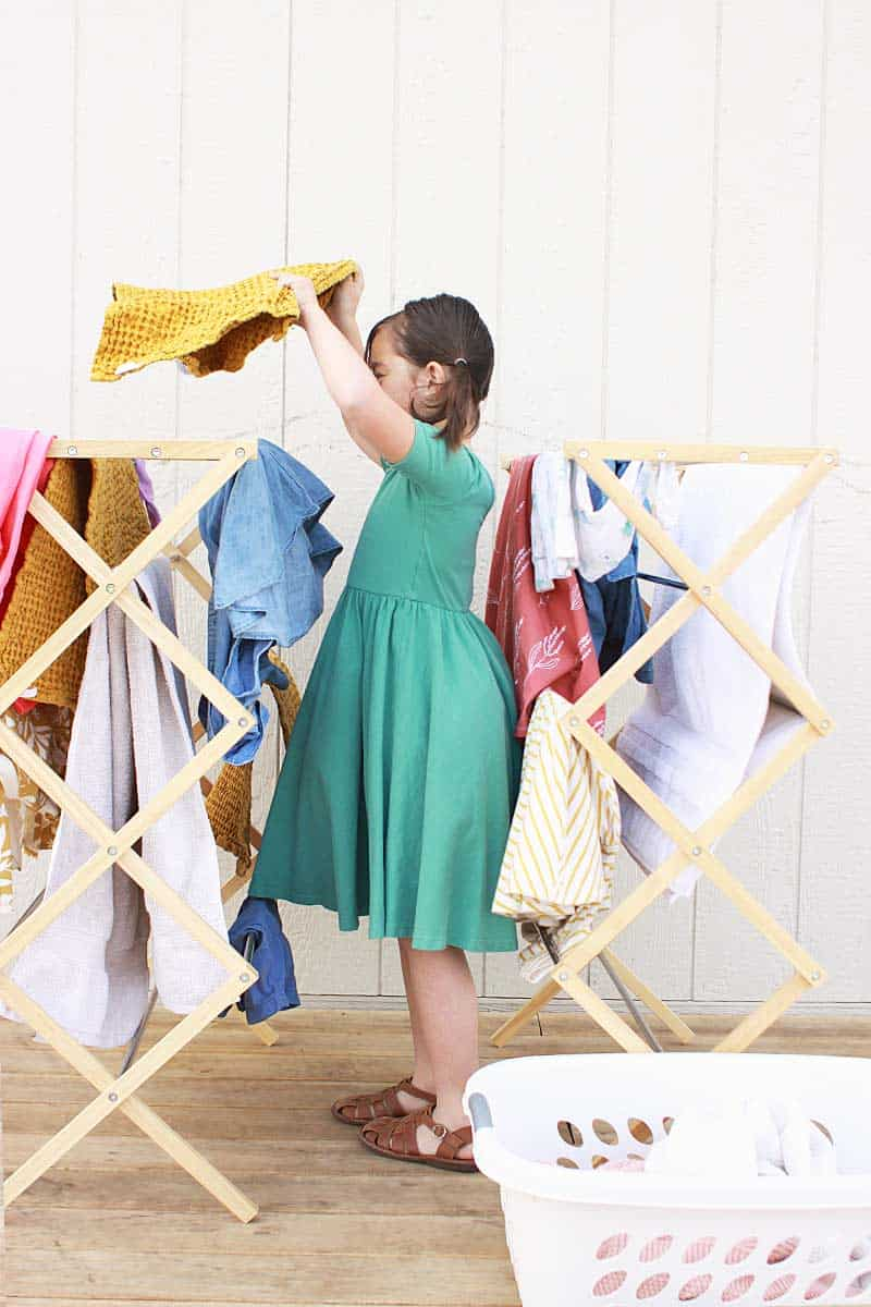 a young girl hanging laundry on drying racks