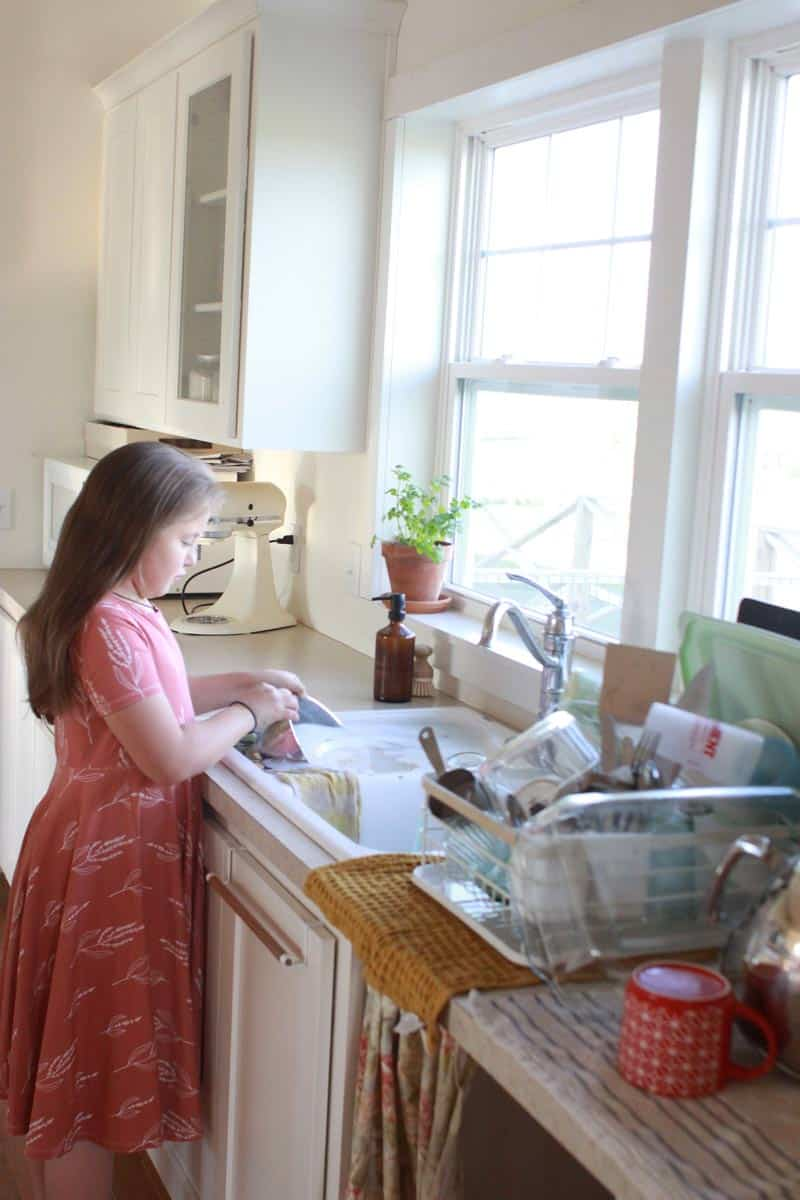 a young girl in a pin dress washing dishes