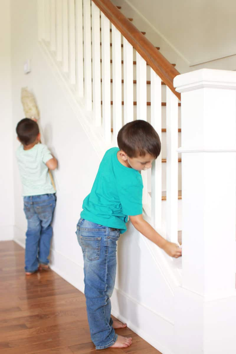 twin toddler boys dusting a stair case together