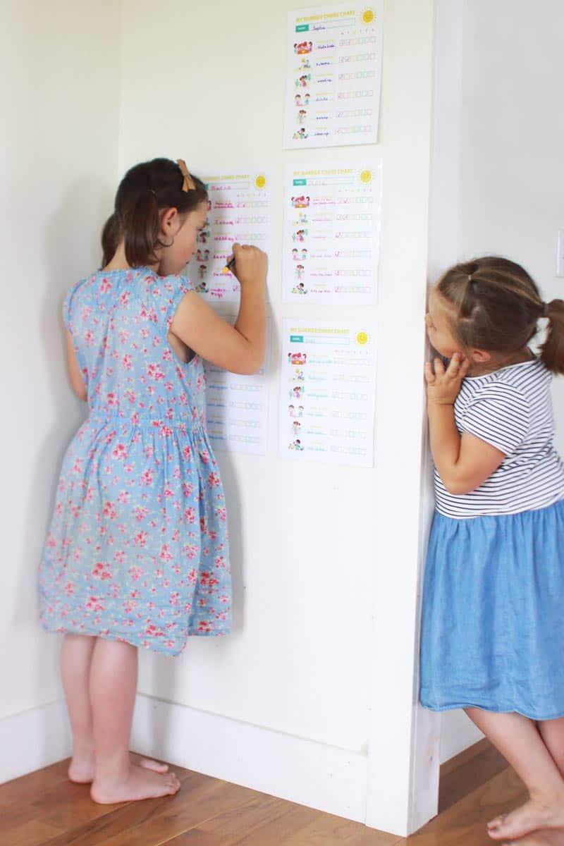 2 girls using dry erase markers on laminated chore charts