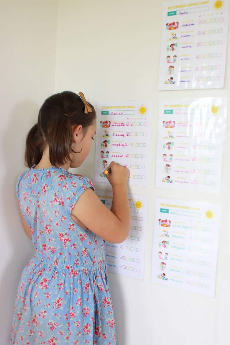 a girl writing with a dry erase marker on a laminated chore chart