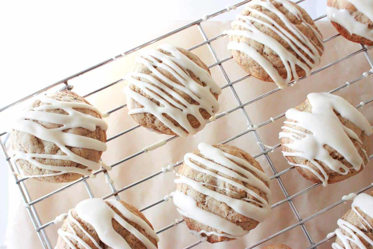 thick soft cookies with coffee grounds in the dough on a wire rack. Icing is drizzled on top.