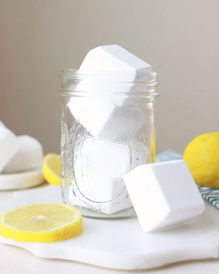 a mason jar full of toilet cleaner bombs and sliced lemons laying on the table around
