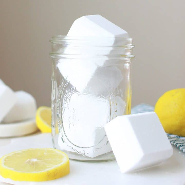 a mason jar of homemade toilet cleaner bombs and sliced lemons laying on the table around