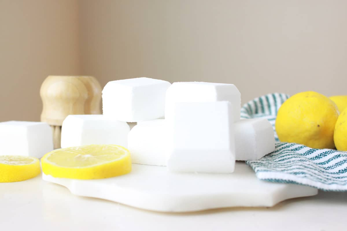 a marble cutting board with toilet bowl cleaner bombs and sliced lemons