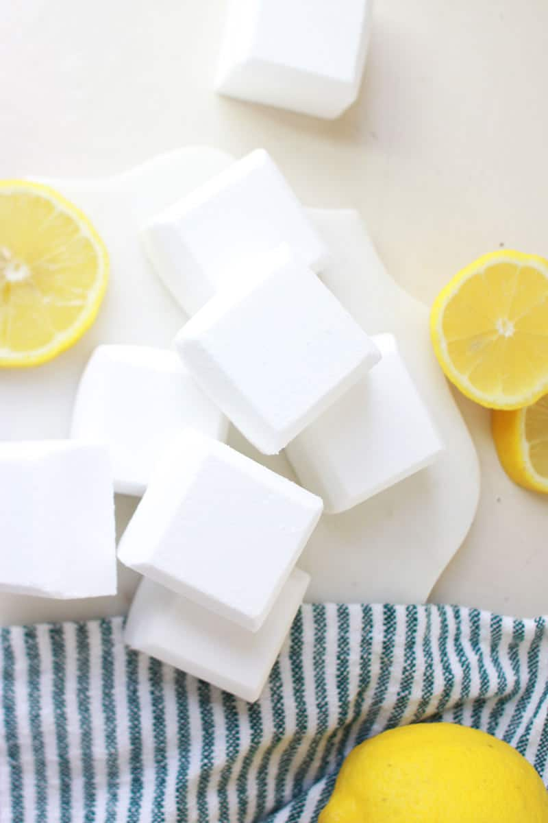 a marble cutting board with toilet cleaner bombs and sliced lemons