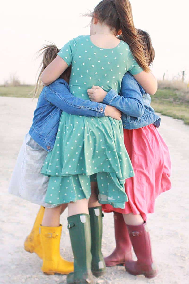 3 sisters in pretty modest dresses and denim jackets and hunter rain boots hugging