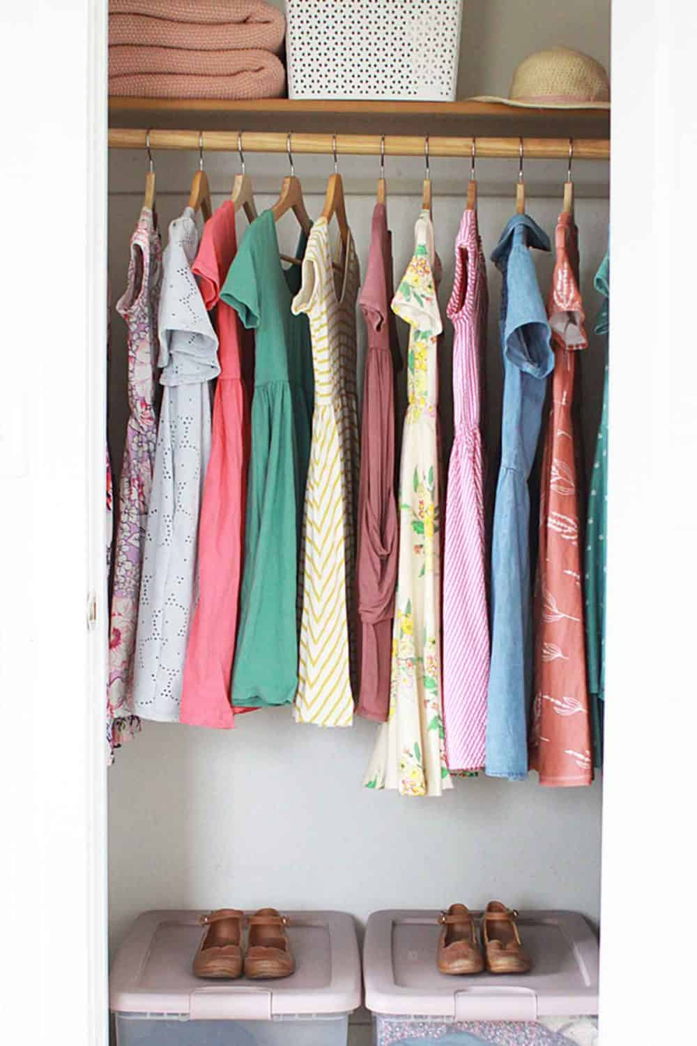 a closet of pastel dresses hanging and two storage totes on the floor