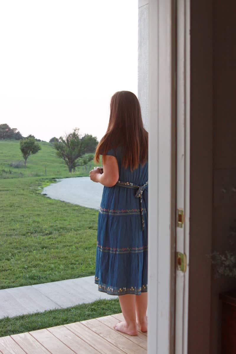 a girl standing on a porch in the evening