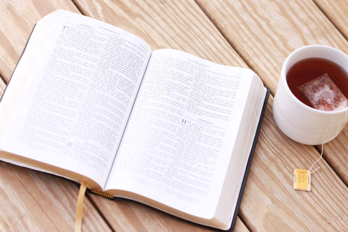 the bible and a cup of tea on a porch in the evening