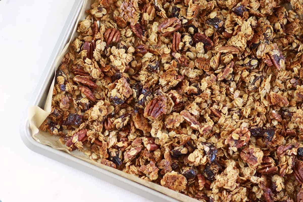 a sheet pan lined with parchment paper homemade granola with pecans and dates