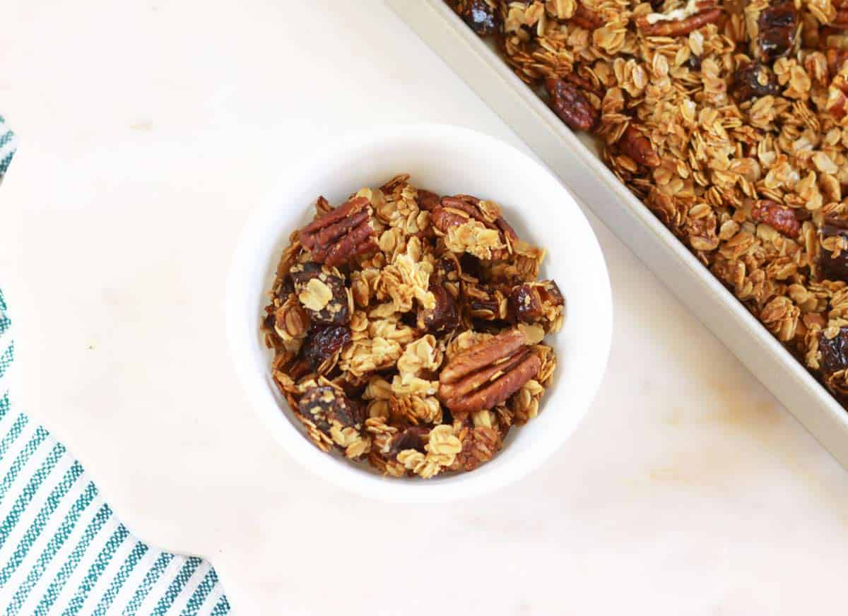 a small bowl and a sheet pan with homemade granola on them