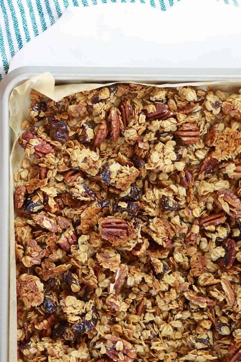 a sheet pan lined with parchment paper of homemade granola with pecans and dates in it